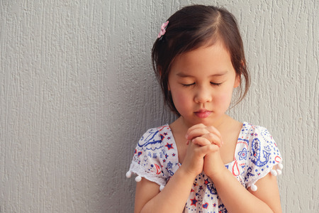 asian little girl praying with eyes closed Фото со стока