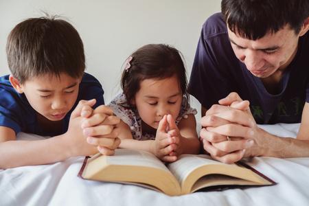 ouder en kinderen bidden op het bed, familie bidden samen