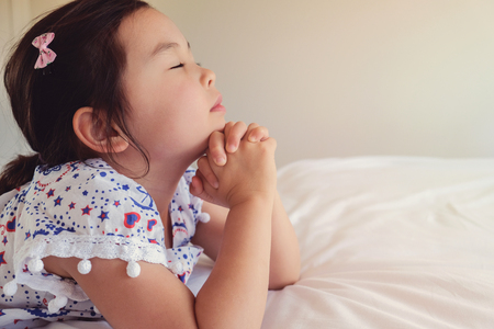asian little girl praying on the bed