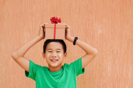 크리스마스 선물 상자를 들고 행복 아시아 소년 아이 미소
