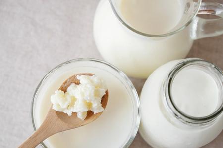 유기농 probiotic 우유 kefir 곡물, 유리 그릇에 kefir 우유 나무 숟가락에 티벳 어 버섯