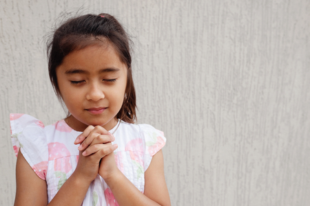 multicultural hispanic girl child praying with eyes closed, christianity faith concept Reklamní fotografie