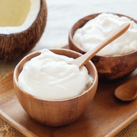 organic coconut yogurt in wooden bowl, dairy free yogurt, probiotic food Stock Photo