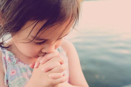 little multiethnic girl praying, kid, child pray conceptม shallow DOF