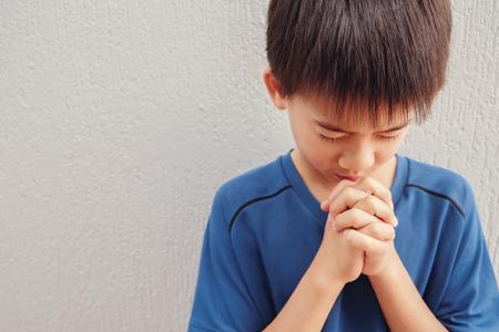 asian boy child praying with eyes closed