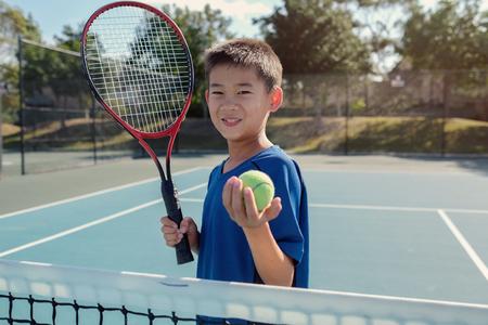 Young tween Asian boy tennis player on outdoor blue court