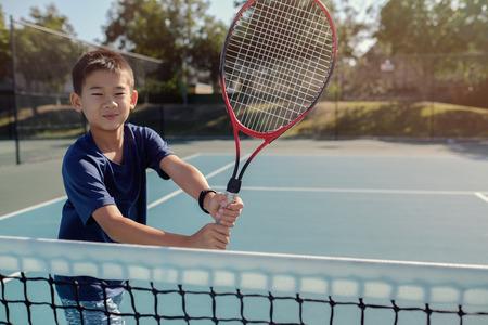 옥외 파란 법원에 젊은 트윈 아시아 소년 테니스 선수