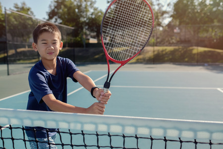 Young tween Asian boy tennis player on outdoor blue court