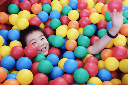 Asian boy having fun in ball pit, indoor play Banque d'images
