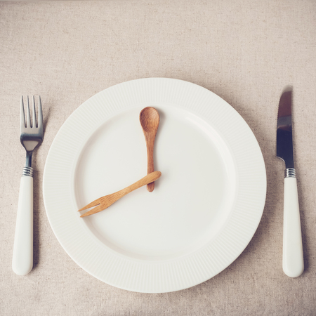 white plate with knife and fork, Intermittent fasting concept, ketogenic diet, weight loss Foto de archivo