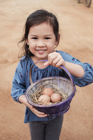 Cute young girl holding basket of fresh organic chicken eggs, Easter activity for kids