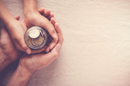 niño y adulto sosteniendo frasco de dinero, donación, concepto de ahorro Foto de archivo