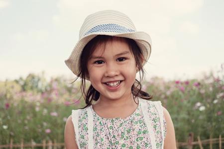 Cute multicultural Asain girl smiling in flower field