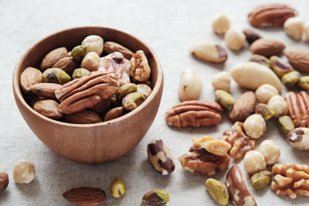 mixed nuts in wooden bowl, healthy fat and protein food