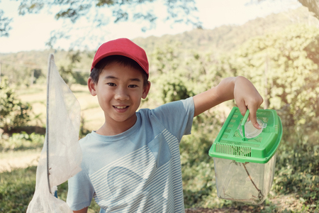 Asain boy catching butterfies with a net and holding a box of insects, outdoor activity for kid, homeschooling education and learn through play concept
