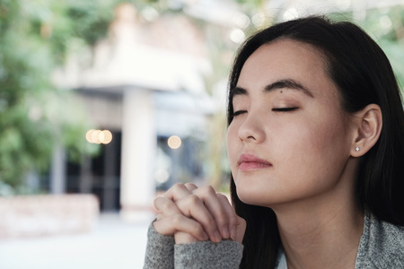 Young Asian woman praying with eyes closed