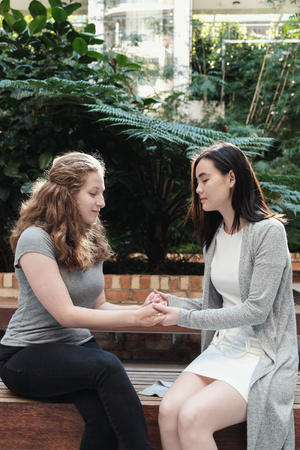 Young multicultural women holding hands while praying