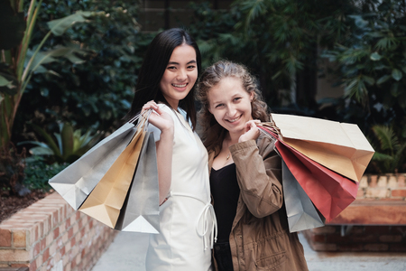 Young multicultural women holding shopping bags 版權商用圖片