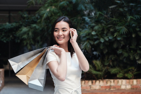 Young Asian woman on the phone holding shopping bags