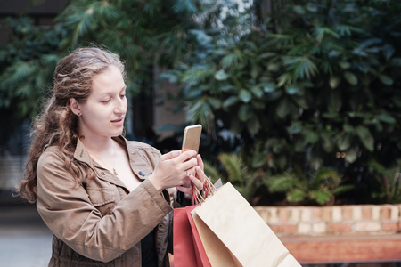 Young woman holding shopping bags and using smartphone, online shopping 版權商用圖片