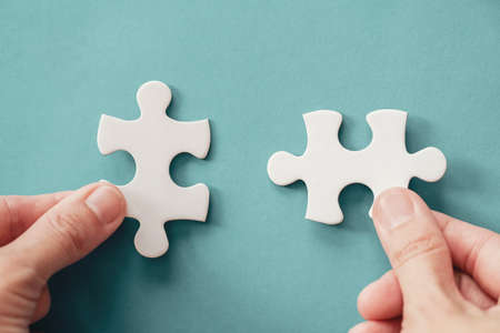 Hands with jigsaw puzzle pieces, Business strategy planning, Alzheimer's disease, Autism and mental health concept Foto de archivo