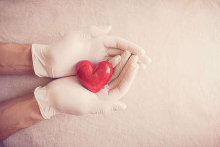 Doctor hands with medical gloves holding red heart, health insurance, donation, charity during covid-19 coronavirus pandemic, saving life, thank you and appreciation to doctor Stockfoto