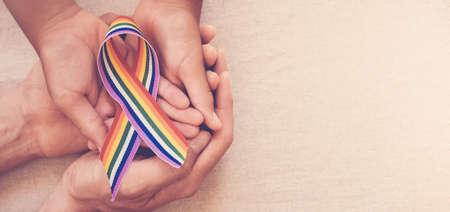 Hands holding gay pride rainbow ribbon for LGBT awareness banner