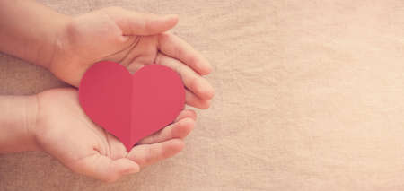 hands and red heart, health insurance, donation and charity concept Stockfoto