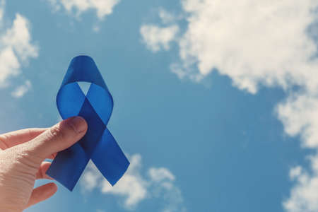 Hand holding blue ribbon on blue sky background , Prostate Cancer Awareness, Men health awareness, November blue, International Men's Day, world diabetes day Stock Photo