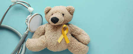 Children soft toy brown bear with yellow gold ribbon and stethoscope, Childhood cancer awareness