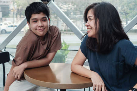 Lifestyle portrait of Asian mother and son spending time together in an urban cafe