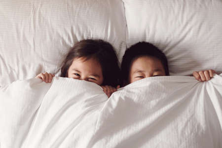 Happy young Asian brother and sister covering their faces with blanket and peeking out cheerfully in the morning
