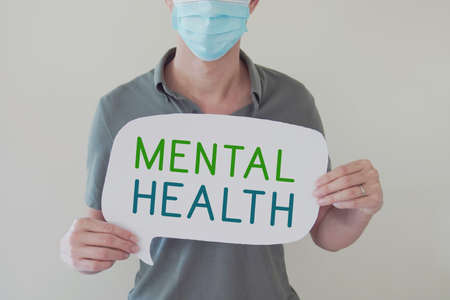 Man wearing mask holding sign MENTAL HEALTH, need counseling help