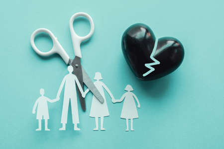 White scissor cutting family paper cut out holding black heart balloon on blue background, causes and effects on child development and behavior of dysfunctional family, divorce broken home concept, mental health Stock Photo