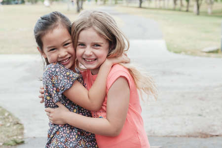 Happy and healthy mixed race young little girls hugging and smiling in the park, best friend kids and children friendship concept