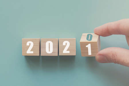 Hand flipping over wooden block of 2020 to 2021, New Year Resolutions, business concept
