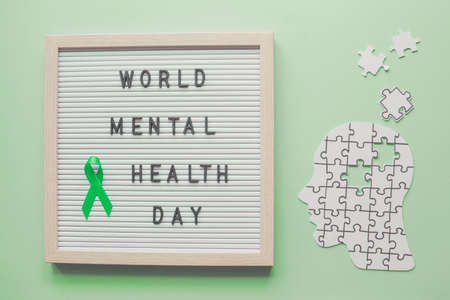 World mental health day and green ribbon on letter board with head and puzzle paper cutout