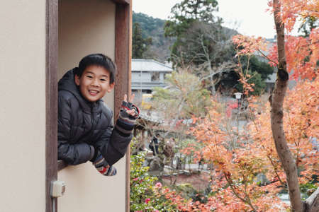 Happy Asian preteen boy smiling with hand gesture v sign in front of Japanese red maple leaves tree in Kyoto Japan Autumn, preteen travel