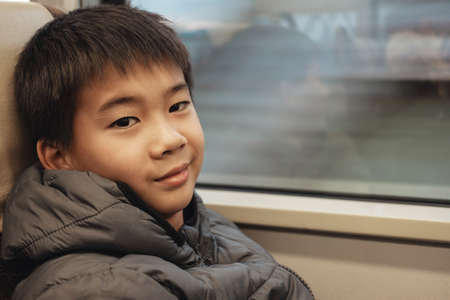 Portrait of tween mixed Asian boy in public train, preteen travel tourist on vacation in Japan winter