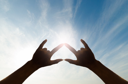 el mundo en tus manos: two silhouette human hand in beautiful shape of love against the sky and sun.