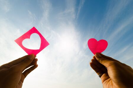 el mundo en tus manos: silhouette human hand with pink paper shape of heart love against the sky and sun.