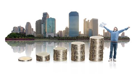 A man happy success in business stand with coin stacking up and high building city on white background. start up, business, real estate, property, financial concept.