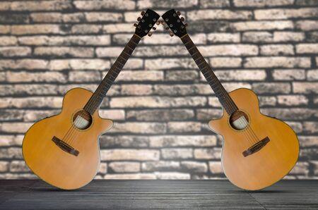 due chitarra acustica sul pavimento di legno su sfondo di muro di mattoni.