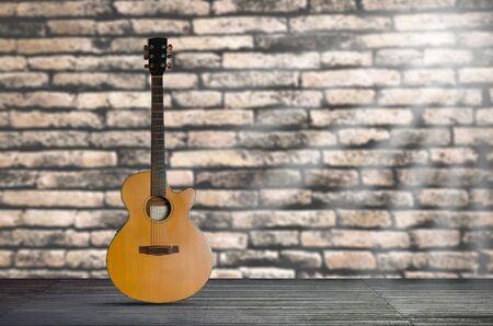 chitarra acustica sul pavimento di legno su sfondo di muro di mattoni.