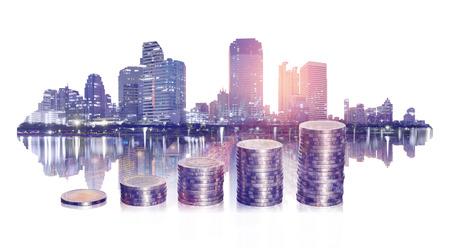 double exposition de la finance d'entreprise avec empilement de pièces et ville sur fond blanc. concept commercial et financier.