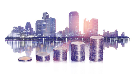 double exposure of business financial with coin stacking and city on white background. business and financial concept.
