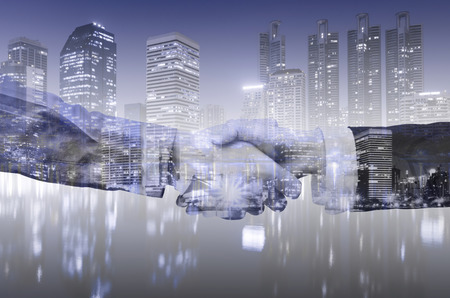 double exposure of business shaking hand between business man and business woman with night city background. success and complete dealership business deal complete or teamwork partnership concept. 写真素材