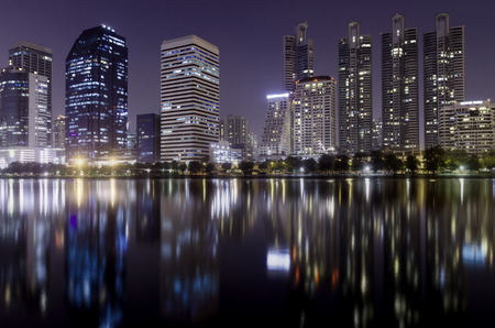 light from modern building bright in night city with skyline symmetric water mirror reflection. night cityscape concept.