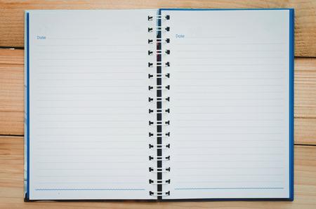 papel de cuaderno vacío y línea azul con espacio de copia abierto en la mesa de madera.