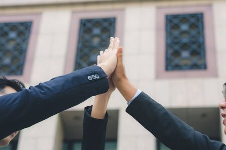 teamwork concept of diversity multiethnic business people with group high five hands bump for relationship and success together front of office building.